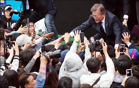 문재인 더불어민주당 대선후보가 18일 오후 전북 전주시 전북대 옛 정문 앞에서 열린 유세에서 시민들의 손을 잡고 있다 ⓒ데일리안
