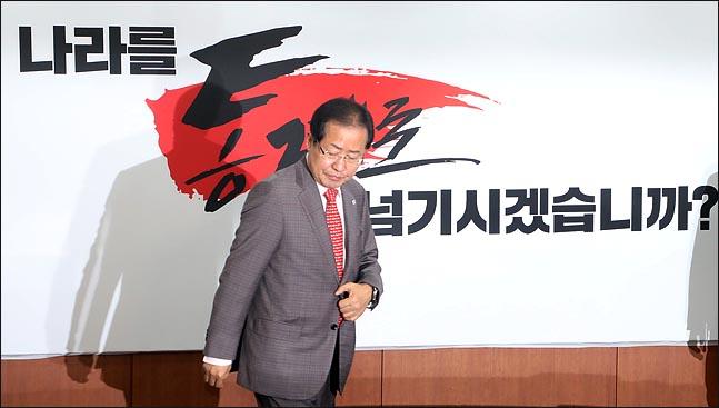 홍준표 자유한국당 대표가 4월 25일 오전 서울 여의도 당사에서 지방선거 필승 슬로건 '나라를 통째로 넘기시겠습니까'를 공개한 뒤 자리에 앉고 있다. ⓒ데일리안 박항구 기자