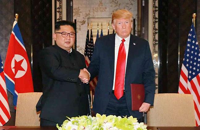 김정은 북한 국무위원장과 도널드 트럼프 미국 대통령이 12일 공동성명에 서명한 뒤 악수하고 있다.ⓒ연합뉴스