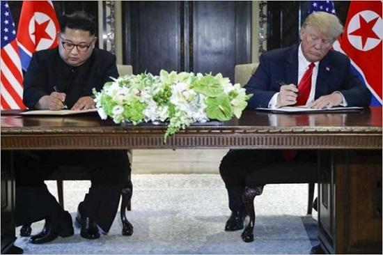 도널드 트럼프(오른쪽) 미국 대통령과 김정은 북한 국무위원장이 지난 12일 북미정상회담 합의문에 서명하고 있다. ⓒCNN