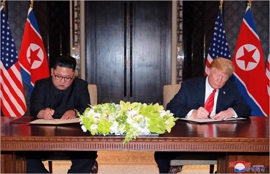 김정은 북한 국무위원장과 도널드 트럼프 미국 대통령이 지난 12일 싱가포르에서 개최된 북미정상회담에서 공동 합의문에 서명하고 있다.ⓒ연합뉴스