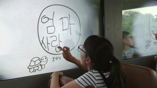 통학버스에 구현된 '스케치북 윈도우' 기술을 이용해 창문에 글씨를 쓰고 있는 어린이의 모습.ⓒ현대자동차그룹