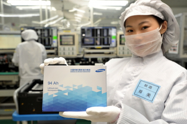 올 상반기 전기차와 에너지저장장치(ESS) 수요로 중대형 배터리는 긍정적인 실적을 거둘 전망이다. 사진은 중국 산시성 시안 소재 삼성SDI 공장의 한 직원이 전기자동차용 배터리를 들어 보이고 있는 모습.ⓒ삼성SDI