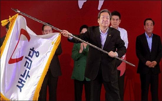 김무성 자유한국당 전 대표최고위원이 지난 2014년 7·14 전당대회에서 대표최고위원으로 선출된 직후, 당기를 건네받아 휘날리고 있다. ⓒ데일리안 박항구 기자