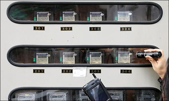 정부가 여름철마다 뜨거운 감자로 떠오르는 '주택용 전기요금 누진제'에 메스를 들었다. 사진은 한 전기검침원이 서울 주택가에서 전기계량기를 확인하는 모습.ⓒ연합뉴스
