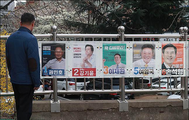 4.3 재보궐 선거 공식 선거운동 첫날인 21일 오후 창원 성산구의 한 아파트에 붙은 벽보를 유권자가 보고 있다. ⓒ데일리안 류영주 기자
