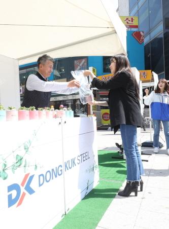 장세욱 동국제강 부회장이 철의 친환경성을 홍보하기 위한 '그린 캠페인' 일환으로 임직원들과 15일 서울 마포에서 한 시민에게 철로 만든 미니 화분을 나눠주고 있다.ⓒ동국제강