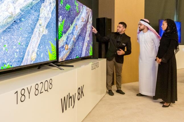 삼성전자 한 관계자(맨 왼쪽)가 17일(현지시간) 아랍에미리트 두바이에 위치한 릭소스 호텔에서 개최된 2019년형 QLED TV 출시 행사에서 관람객들에게 기능을 설명하고 있다.ⓒ삼성전자
