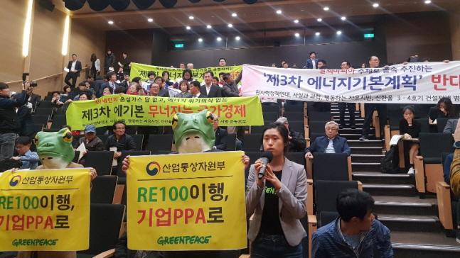 이유니 그린피스 활동가는 19일 서울 강남구 코엑스에서 열린 '제3차 에너지기본계획 수립을 위한 공청회'에서 정부가 에너지전환 정책에 속도를 높여야 한다고 주장하고 있다. 뒤로는 울진군 주민들과 원자력정책연대 관계자들이 '3차 에너지기본계획 반대' 현수막을 펼쳐 보이고 있다.ⓒ데일리안 조재학 기자