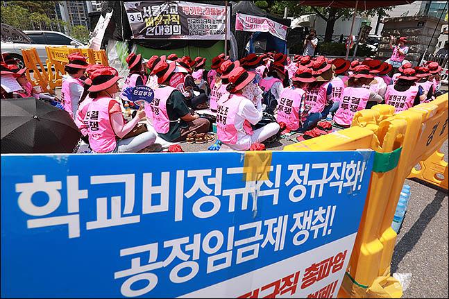 급식조리원 등 학교 비정규직 노동자들이 청와대 앞에서 집회를 열어 교육 당국과 청와대를 비판하면서