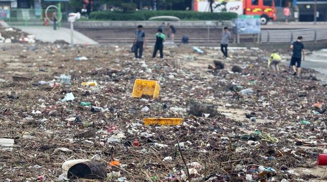 21일 부산 수영구 광안리해수욕장 백사장에 쓰레기와 해초가 뒤섞여 파도에 밀려와 있다.ⓒ연합뉴스