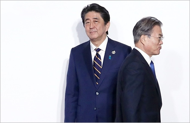문재인 대통령이 지난달 28일 일본 오사카에서 개최된 G20 정상회의 공식환영식에서 아베 신조 총리와 악수한 뒤 이동하고 있다. ⓒ연합뉴스