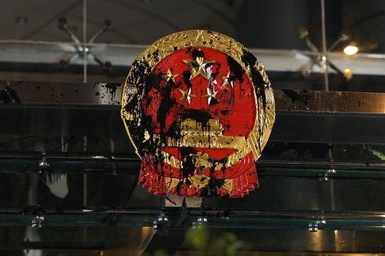 21일 홍콩 시위대는 홍콩 주재 베이징 연락판공실 건물에 걸려 있는 국가 휘장에 먹물을 뿌렸다. ⓒEPA=연합뉴스