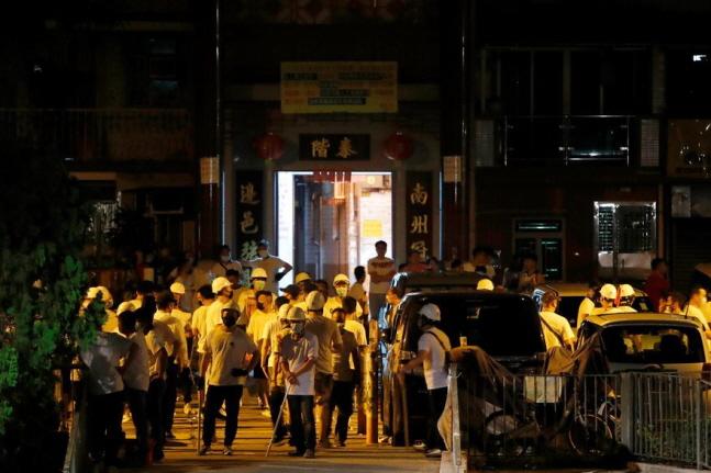 지난달 21일 밤 홍콩 위안랑(元朗) 전철역에서 열린 범죄인 인도법(송환법) 반대 집회 참가자들을 공격한 흰 티셔츠와 헬멧 차림의 남성들이 몰려 있다.ⓒ연합뉴스