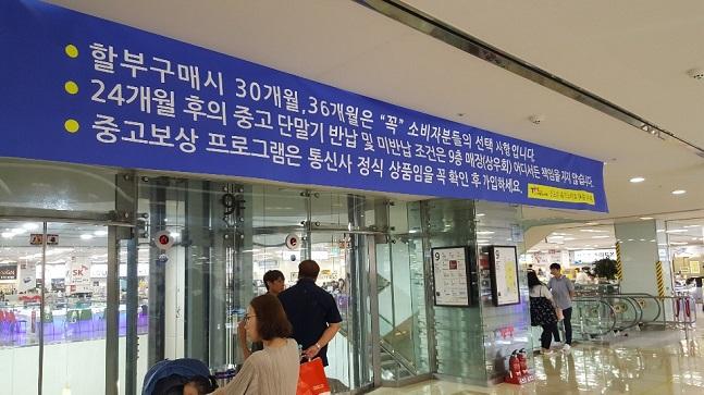지난 25일 서울 신도림 테크노마트 9층 휴대폰 집단상가에 '중고보상 프로그램은 통신사 정식 상품임을 꼭 확인 후 가입하세요.'라는 문구가 적힌 현수막이 걸려있다.ⓒ데일리안 김은경 기자