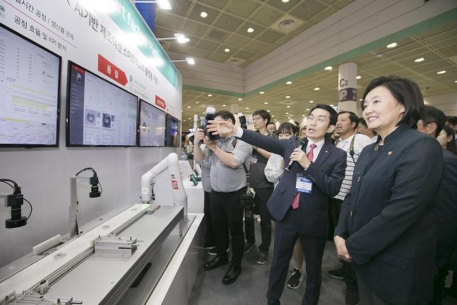 이용규 KT 5G플랫폼개발단장(상무·오른쪽 두 번째)이 26일 오전 서울 삼성동 코엑스에서 열린 'ITS 2019(제20회 중소기업기술혁신대전)' KT 전시관을 방문한 박영선 중소벤처기업부 장관(오른쪽 첫 번째)에게 5G 기반 스마트팩토리 플랫폼을 설명하고 있다.ⓒKT