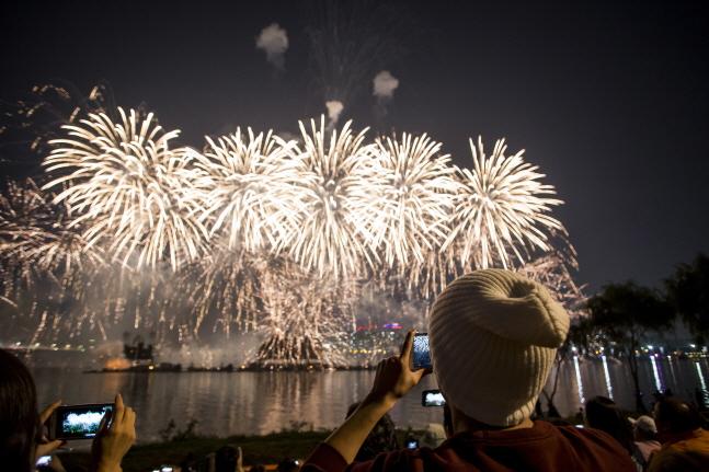 지난해 서울세계불꽃축제에서 관람객이 불꽃쇼를 스마트폰으로 촬영하고 있는 모습.(자료사진)ⓒ한화