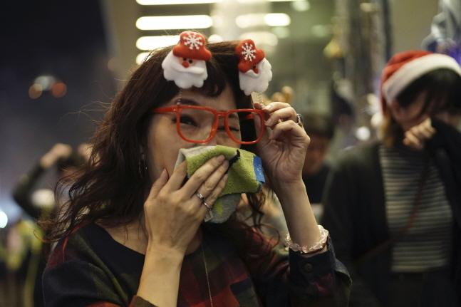 24일 밤 홍콩의 쇼핑몰에서 한 여성이 최루탄 연기에 고통스러운 표정을 짓고 있다. 이날 도심 곳곳에서 수천명이 민주화 시위를 벌였다.ⓒ뉴시스