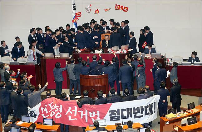 27일 오후 열린 국회 본회의에서 문희상 국회의장이 의장석 진입을 차단한 자유한국당 의원들의 저지를 뚫고  의장석에 앉은 가운데 자유한국당 의원들이 피켓을 던지며 항의하고 있다. ⓒ데일리안 박항구 기자