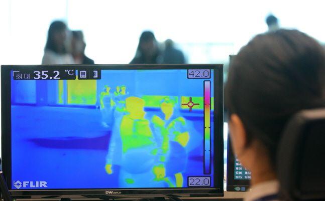 인천국제공항 제2터미널 입국 게이트에서 질병관리본부 국립검역소 직원이 열화상 카메라로 승객들의 체온을 재고 있다.