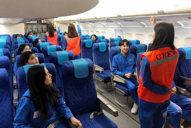 학생들이 에어부산 훈련복을 입고 모의 항공기 훈련장(MOCK-UP)에서 안전 교육을 받고 있다.ⓒ에어부산