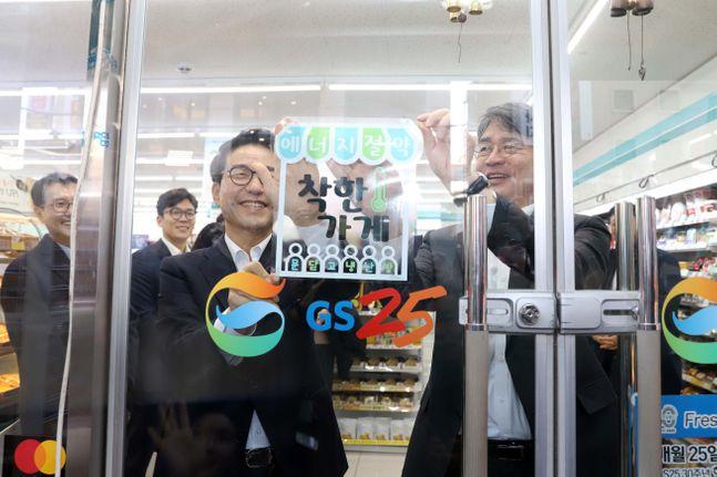 김창섭 한국에너지공단 이사장(오른쪽)이 17일 조윤성 GS리테일 사장과 GS25 역삼 프리미엄점을 방문해 에너지절약 착한가게 1호점 인증 에너지절약 '착한가게 스티커'를 부착하고 있다.ⓒ한국에너지공단