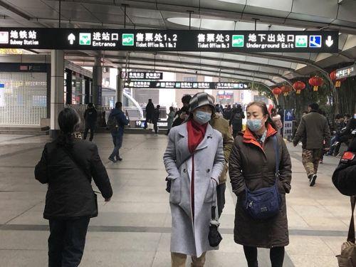 21일 중국 후베이성 우한시 한커우 역 앞 거리에서 마스크를 쓴 시민들이 걷고 있다.