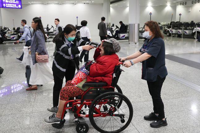 홍콩 공항에서 지난 23일 한 보건 당국자가 한 승객의 체온을 재고 있다. 홍콩에서 우한발 폐렴에 감염된 두번째 확진자가 나오면서 당국이 방역을 강화하고 있다.ⓒAP/뉴시스