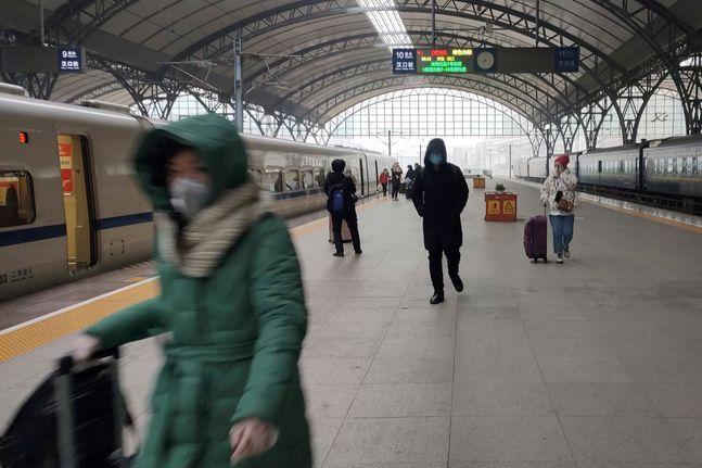 중국 우한에서 지난 23일 봉쇄령이 내려지기 직전 몇몇 사람들이 기차역 플랫폼에서 마스크를 쓴 채 걸어가고 있다.ⓒAP/뉴시스