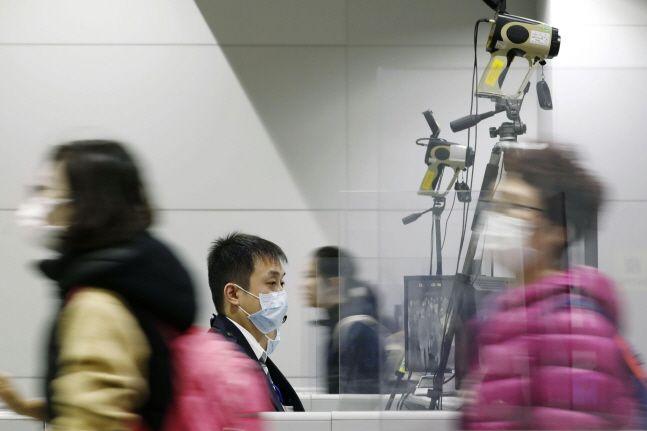 일본 오사카에 위치한 간사이 공항에서 마스크를 쓴 사람들이 체온측정 카메라 앞을 지나치고 있다.ⓒ뉴시스