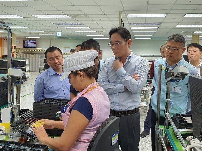 이재용 삼성전자 부회장(오른쪽 세번째)이 27일(현지시간) 브라질 마나우스 공장 생산라인 내 스마트폰 조립 공정을 살펴보고 있다.ⓒ삼성전자