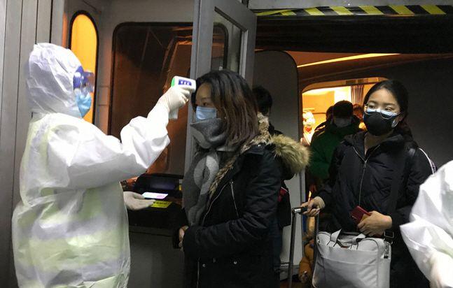 정부가 우한폐렴(신종 코로나바이러스 감염증)의 발원지인 중국 우한에 체류 중인 교민과 유학생을 철수시키기 위해 전세기 투입을 고려 중인 가운데 탑승 신청자가 700명에 육박한 것으로 나타났다. 사진은 지난 22일 중국 베이징 공항에서 보호복을 입은 보건 관계자들이 우한시에서 도착한 승객들의 체온을 체크하고 있는 모습.ⓒ뉴시스