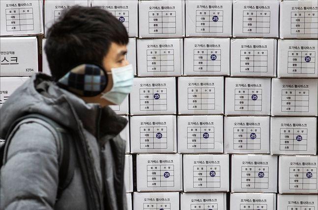 신종 코로나 바이러스 감염증(우한 폐렴)의 확산으로 국내에서도 확진 환자가 발생한 가운데 28일 오후 서울 명동의 한 약국 앞에서 마스크를 착용한 관광객의 너머로 마스크 제품 박스가 쌓여 있다. ⓒ데일리안 홍금표 기자