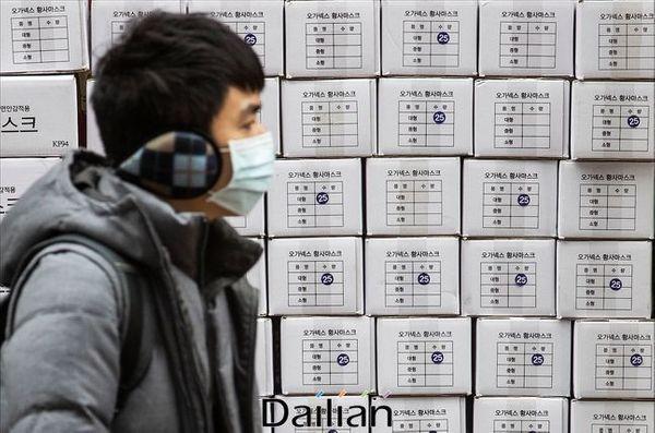 서울 명동의 한 약국 앞에서 마스크를 착용한 관광객의 너머로 마스크 제품 박스가 쌓여 있다(자료사진). ⓒ데일리안