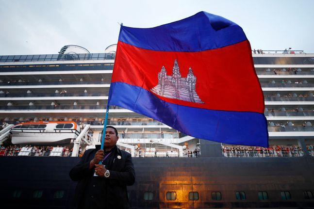 14일(현지시간) 캄보디아 시아누크빌 항구에 입항한 유람선 웨스테르담 앞에서 한 남성이 캄보디아 국기를 들고 서 있다. ⓒ뉴시스