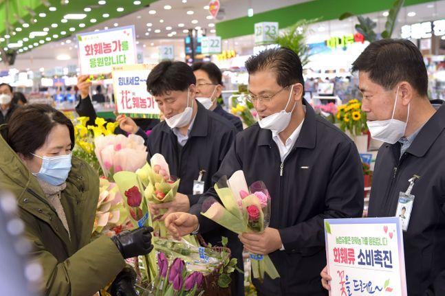 17일 서울 농협 하나로마트 양재점 화훼 행사장에서는 농협유통 나병만 대표이사(오른쪽 두번째) 등 임직원들이 화훼농가를 돕기 위해 고객들에게 꽃을 나눠주고 있다.ⓒ농협유통