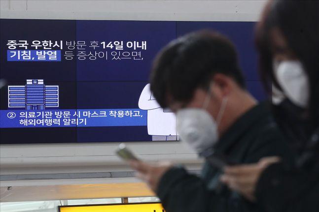 지난달 28일 오전 서울 용산구 서울역에서 마스크를 착용한 시민들 너머로 신종 코로나바이러스 감염증(코로나19) 관련 영상이 나오고 있다.ⓒ데일리안 홍금표 기자