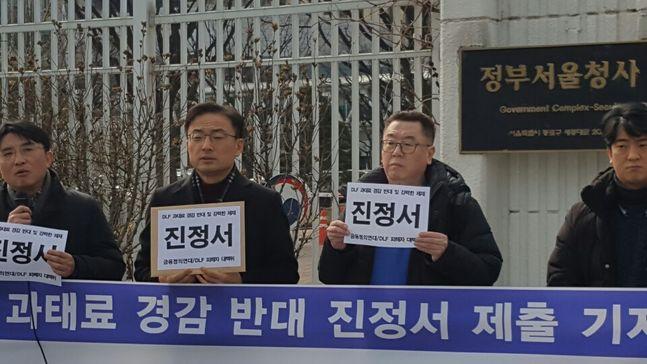 DLF 피해자대책위원회와 시민단체 금융정의연대가 19일 오후 서울 광화문 정부서울청사 앞에서 기자회견을 열고 금융위 산하 증권선물위원회가 DLF사태 관 우리은행과 하나은행의 과태료를 낮춰준 것에 대해