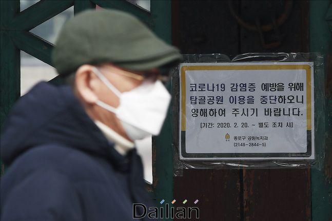 코로나19 감염증 예방을 위해 탑골공원이 폐쇄된 가운데 21일 오전 서울 종로구 탑골공원 입구에서 이용 중단 안내문이 부착된 문 앞으로 마스크를 착용한 시민이 길을 지나고 있다. ⓒ데일리안 홍금표 기자