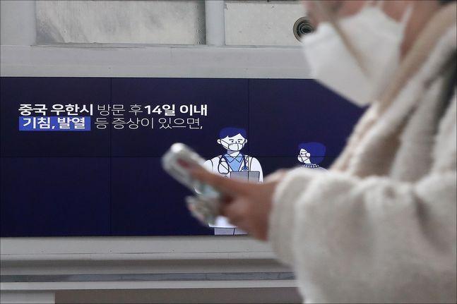 서울 용산구 서울역에서 마스크를 착용한 시민들 너머로 신종 코로나 바이러스 감염증(코로나19) 관련 영상이 나오고 있다. ⓒ데일리안 홍금표 기자