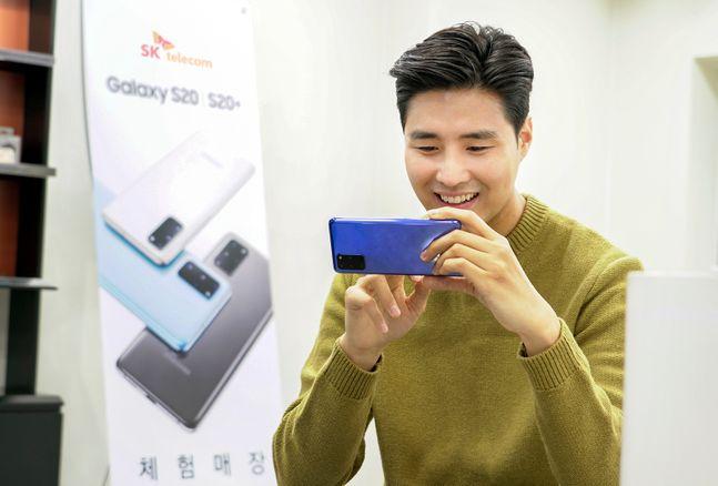 SK텔레콤 홍보모델이 27일 T월드매장에서 삼성전자 '갤럭시S20 플러스' 아우라 블루 모델을 써보고 있다.ⓒSK텔레콤