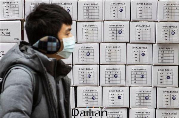 서울 명동의 한 약국 앞에서 마스크를 착용한 관광객의 너머로 마스크 제품 박스가 쌓여 있다.ⓒ데일리안 홍금표 기자
