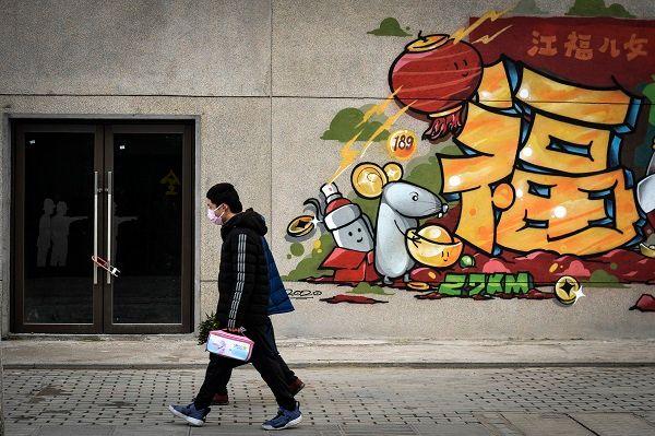 지난 22일(현지시간) 신종 코로나바이러스 감염증(코로나19) 진원지인 중국 후베이성 우한시의 한 폐쇄된 건물 앞을 마스크 낀 남성이 지나가고 있다. ⓒ우한=AP/뉴시스