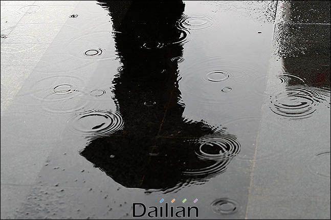 우산을 쓴 시민이 지나가는 모습이 물웅덩이에 비치고 있다(자료사진). ⓒ데일리안 류영주 기자