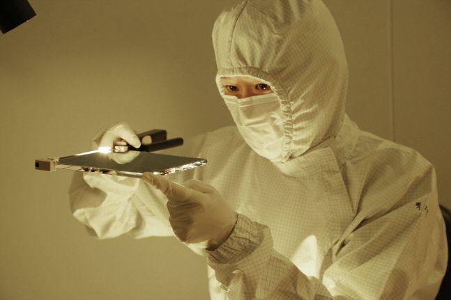 SKC 한 직원이 반도체 노광공정 핵심소재인 블랭크 마스크의 시제품을 검사하고 있다.ⓒSKC