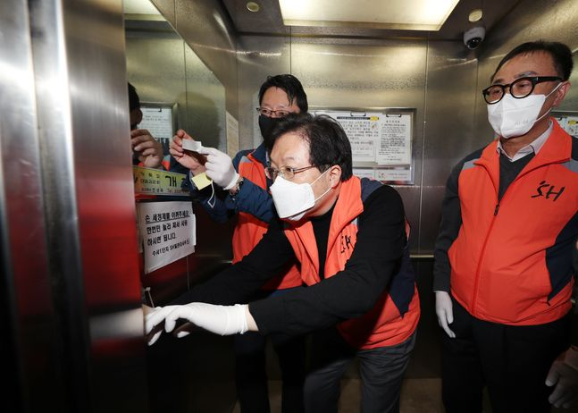 25일 한 임대아파트 승강기에 항균필름을 부착하고 있는 SH공사 임직원.ⓒSH공사