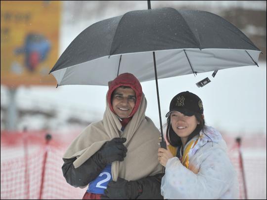 우산을 함께 쓴 참가자와 자원봉사자.