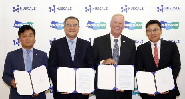 23일 두산중공업 서울사무소에서 열린 두산중공업과 미국 뉴스케일파워(NuScale Power)의 소형모듈원전(SMR, Small Modular Reactor) 사업협력계약 체결식에서 관계자들이 서명 후 기념촬영을 하고 있다. 오른쪽부터 송용진 두산중공업 전략/혁신부문장, 존 홉킨스(John Hopkins) 뉴스케일파워 CEO, 나기용 두산중공업 원자력BG장, 장재성 IBK투자증권 M&A/PE본부장.ⓒ두산중공업