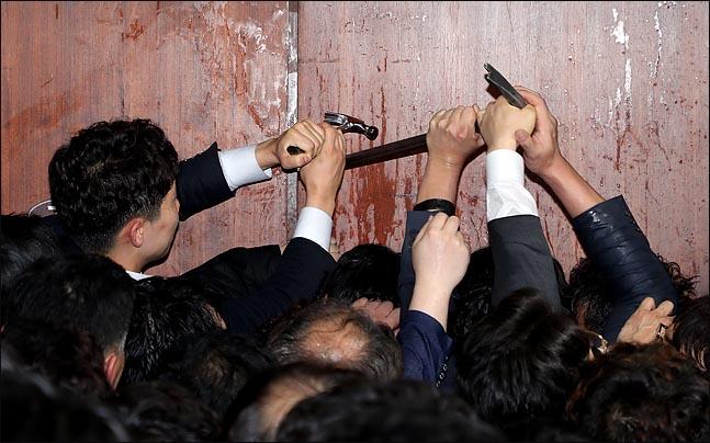 선거제·공수처법 패스트트랙 처리를 저지하기 위한 자유한국당의 국회 점거가 계속되고 있던 지난 4월말 국회본청 의안과 앞에서 국회 관계자들이 장도리와 쇠지레로 문을 열고 있다. ⓒ데일리안 홍금표 기자