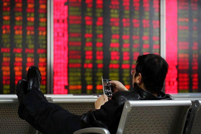지난 6일 중국 베이징의 한 증권사 객장에서 한 남성이 스마트폰으로 시황을 살펴보고 있고 있다.ⓒAP/뉴시스